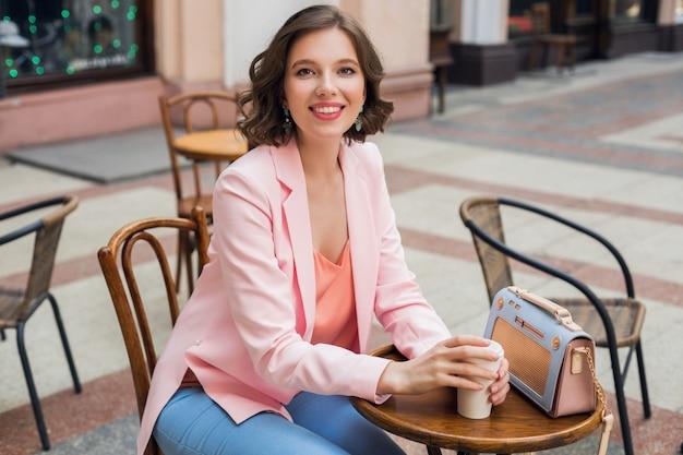 Ritratto di elegante signora sorridente seduta a tavola a bere caffè in giacca rosa tendenza stile estivo, borsa blu, accessori, street style, moda donna