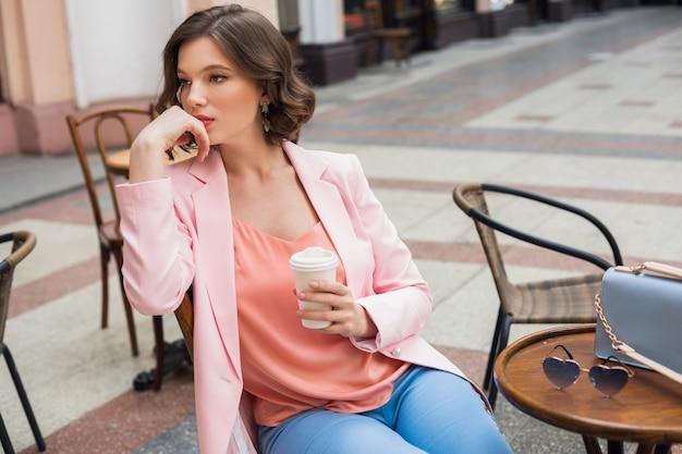 Ritratto di signora pensante alla moda seduta a tavola a bere caffè in giacca rosa tendenza stile estivo, borsa blu, accessori, street style, moda donna