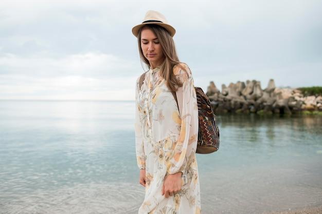 Portrait of stylish traveller walking down the shore