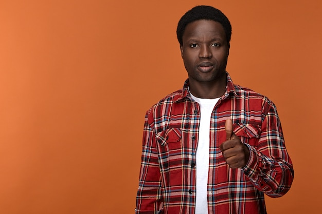 Portrait of stylish trendy looking young afro american man in his twenties posing against blank  wall with thumbs up gesture, expressing approval, satisfaction and positive attitude