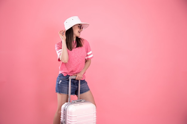 Portrait of a stylish woman in fashionable summer clothes and a white hat on pink with a suitcase for traveling.