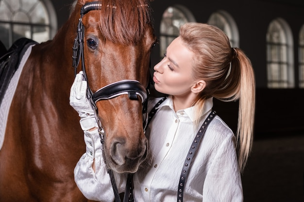Portrait of a stylish woman hugging a thoroughbred horse. love and care concept. mixed media