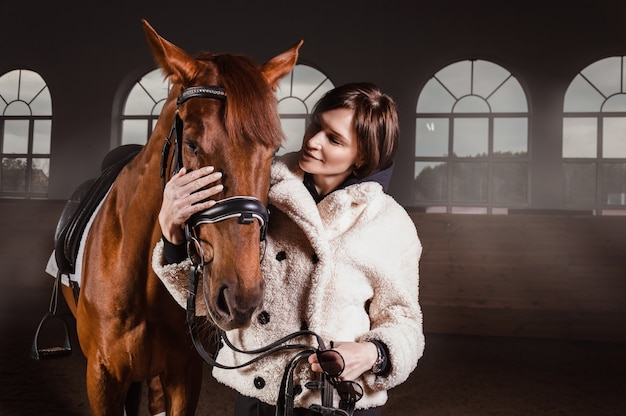Portrait of a stylish woman hugging a thoroughbred horse. love and care concept.