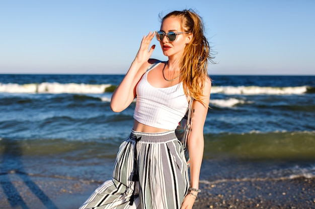 Portrait of stylish woman posing, summer crop top sunglasses and culottes