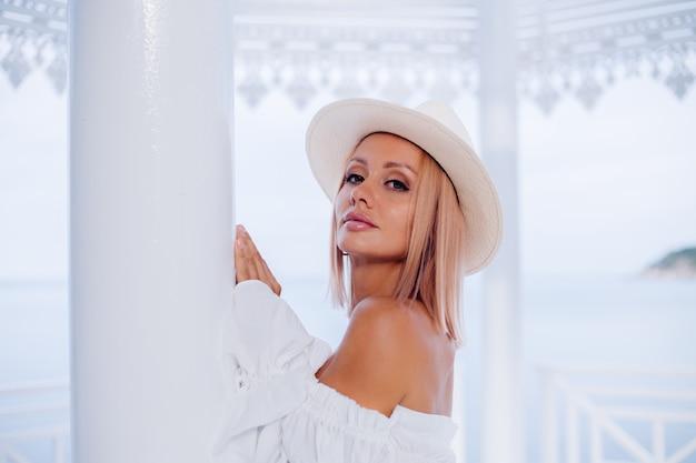 Ritratto di donna alla moda in voluminoso bianco alla moda top e classico cappello di lusso