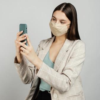 Donna alla moda del ritratto con la maschera facendo uso del cellulare