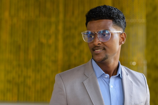 Portrait of stylish young african businessman outdoors wearing eyeglasses and smiling