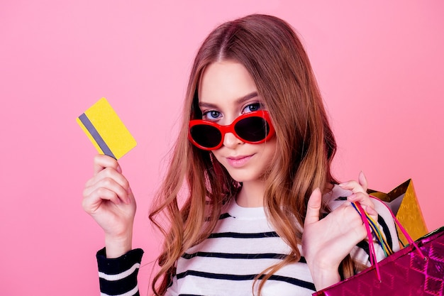 Portrait of a stylish and young attractive woman in a striped sweater and red sunglasses holds many shopping bags and credit card on a pink background in the studio. concept of shopaholism and sale