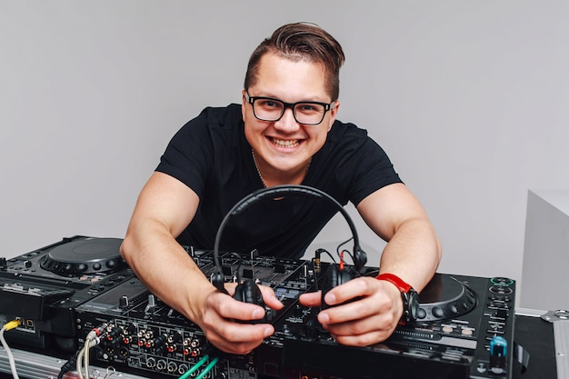 Portrait of stylish young man in formal suit and glasses standing at dj mixer