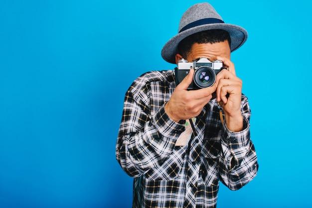 カメラで写真を作る帽子の肖像画スタイリッシュな若い男。タベリング、週末、休日、興奮、観光、真のポジティブな感情を表現し、楽しんで。