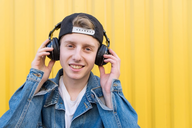 Portrait of a stylish young man who listens to music in wireless headphones on a yellow wall.