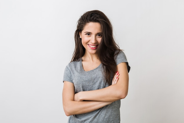 Portrait of stylish young pretty woman smiling in grey t-shirt on , isolated, natural look, long brown hair, crossed arms