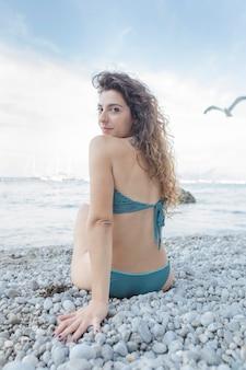 Portrait of stylish young woman in bikini sitting on pebble beach