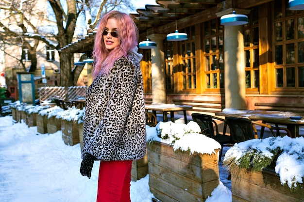 Portrait of stylish young woman posing at the street wearing unusual pink hair, trendy leopard jacket and vintage glasses