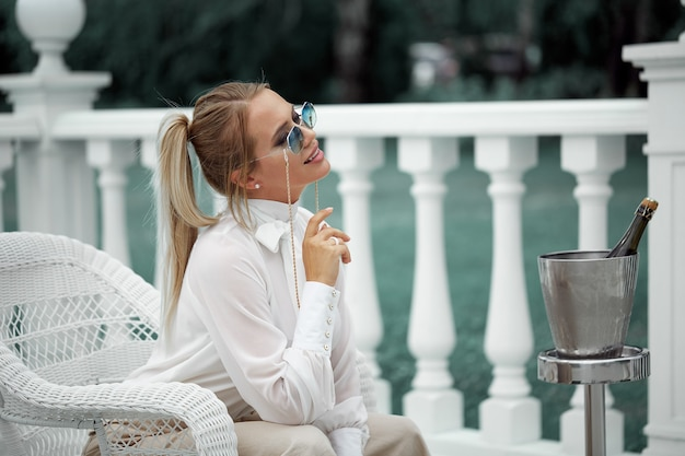 Portrait of a stylish young woman posing in sunglasses, sitting in a white wicker chair