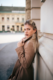 Portrait of stylish young woman in the town street.