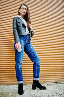 Portrait of stylish young woman wearing on leather jacket with mobile phone at hand