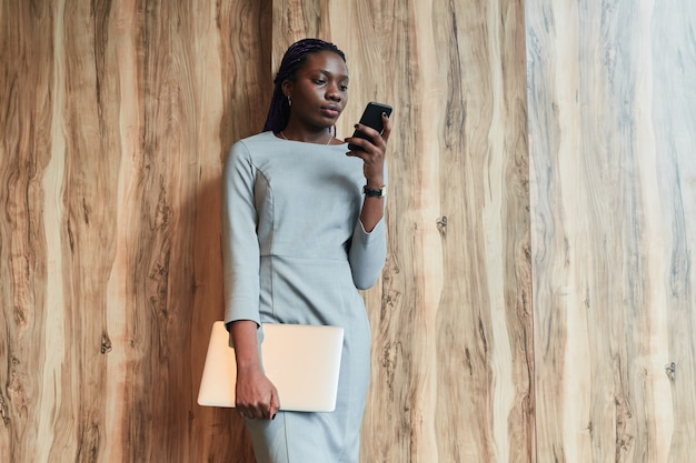 Portrait of successful african-american businesswoman wearing mask and using smartphone while standing in sunlight by wood background, copy space