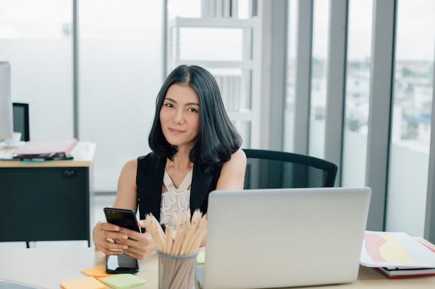 Portrait of successful asian businesswoman using phone and working at modern office
