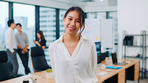 Portrait of successful beautiful executive businesswoman smart casual wear looking at camera and smiling in modern office workplace. young asia lady standing in contemporary meeting room.