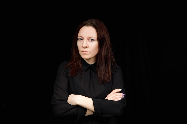 Portrait of successful business woman in  a black shirt with crossed hands on black background.