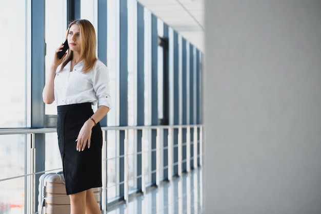 Portrait of successful business woman traveling with case at airport