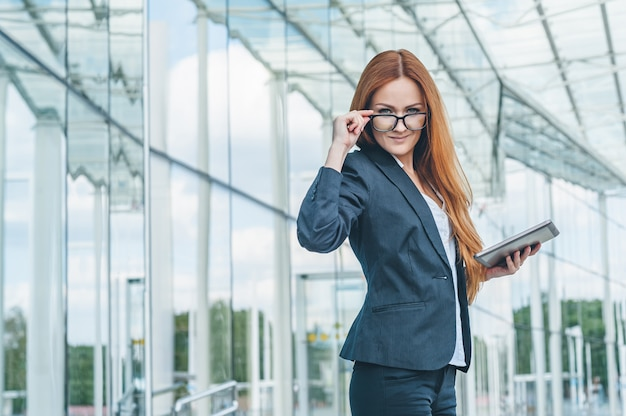 Portrait of a successful business woman wearing glasses, holding a tablet, in the background is a glass business center.