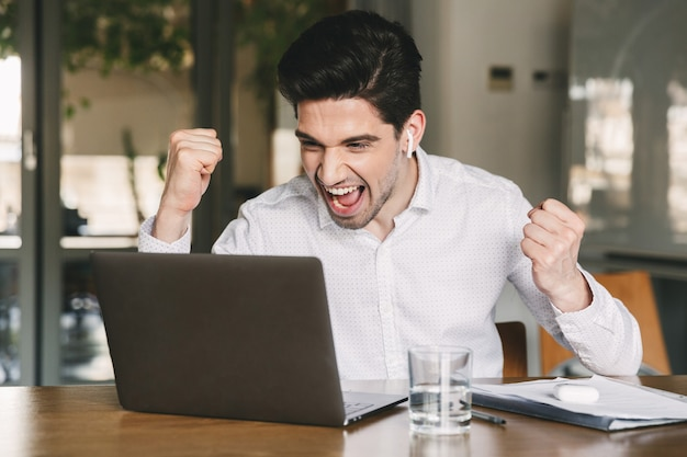 Portrait of successful businessman 30s wearing white shirt and bluetooth earbud screaming and clenching fists, while looking at laptop in office