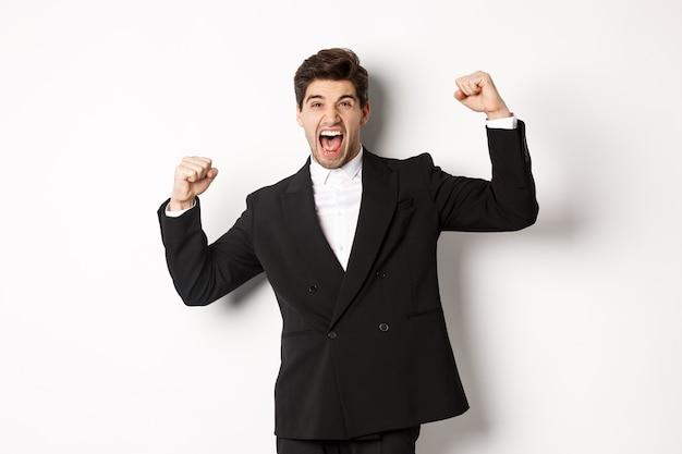 Ritratto di uomo d'affari di successo in abito nero, diventato campione, alzando le mani e gridando sì, trionfando e celebrando la vittoria, in piedi su sfondo bianco.