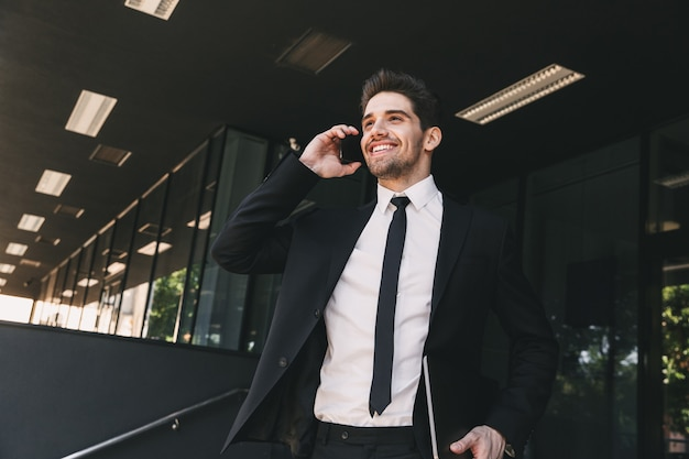 Portrait of successful businessman dressed in formal suit walking outside glass building, and talking on mobile phone
