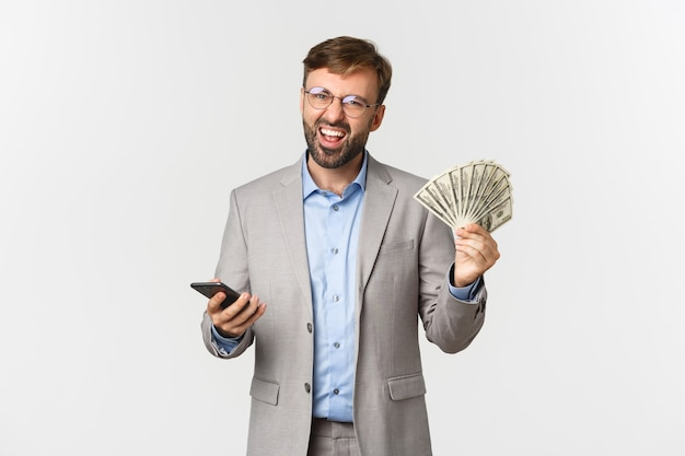 Portrait of successful businessman earn money, holding cash and mobile phone