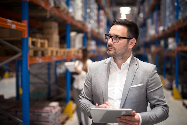 Portrait of successful businessman manager ceo holding tablet and walking through warehouse storage area looking towards shelves