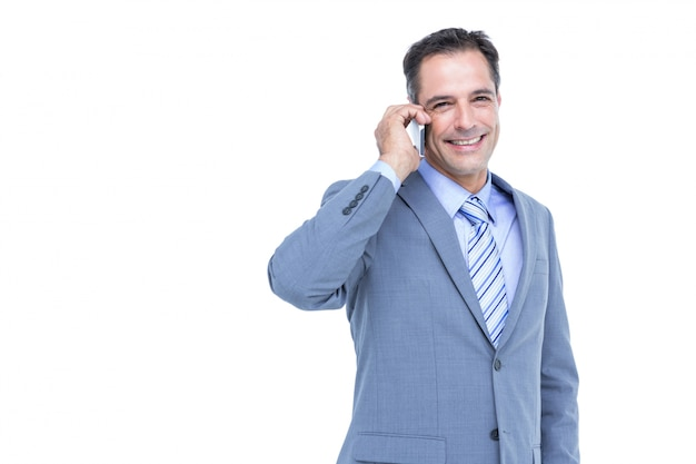 Portrait of a successful businessman on phone against white