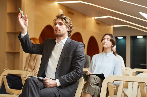 Portrait of successful businessman raising hand to ask question while sitting in audience of contemporary conference hall interior, copy space