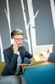 Portrait of successful businesswoman working with laptop in office