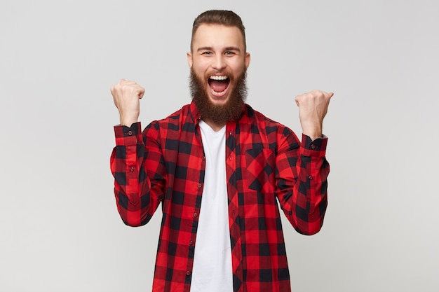 Portrait of a successful cheerful fortunate happy bearded man in checkered shirt clenching fists like winner,celebrates his victory, isolated over white background