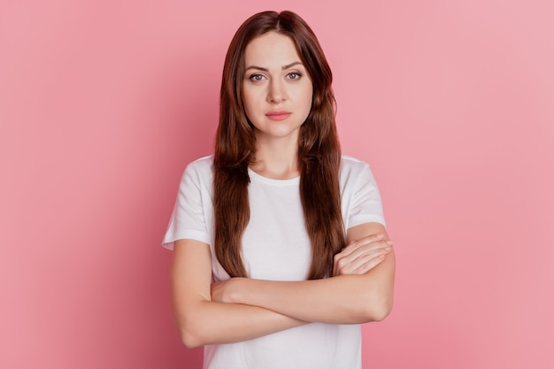 Portrait of successful confident girl crossed hands look camera on pink background