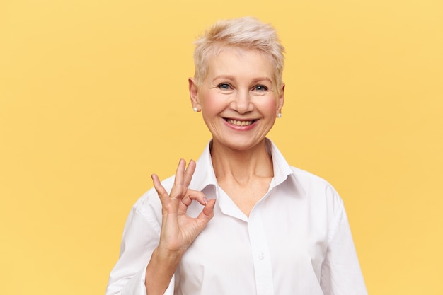 Portrait of successful confident middle aged businesswoman with short dyed hair with broad smile making ok gesture, rejoicing at good profitable deal and great yearly income