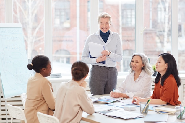 Portrait of successful female boss smiling happily looking at group of colleagues during meeting in modern white office