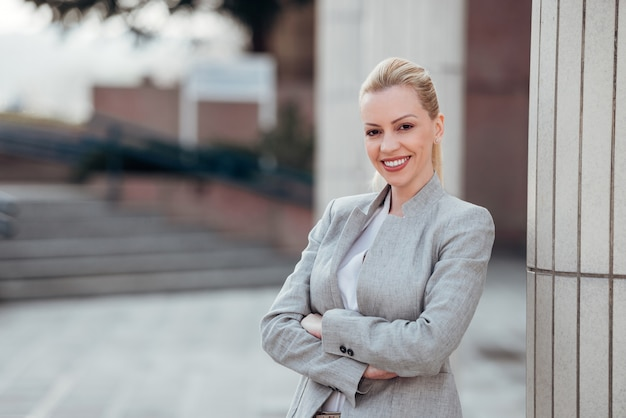 Portrait of a successful female leader outdoors, smiling at camera.