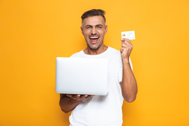 Portrait of successful guy 30s in white t-shirt holding silver laptop and credit card isolated on yellow