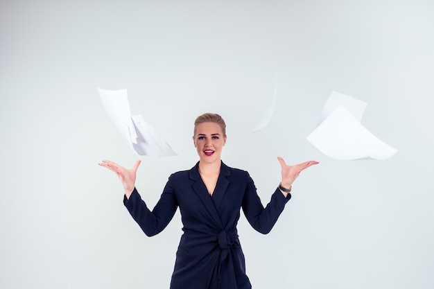 Portrait of successful happy business woman glasses blonde hairstyle perfect make-up red lips in stylish black suit throwing paper up, in studio white background isolate.freedom of deadline