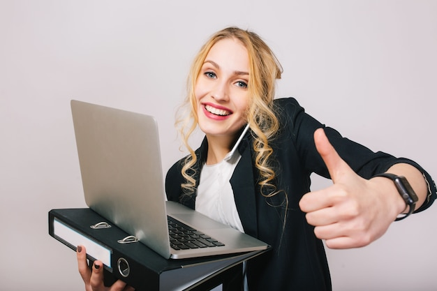 Portrait successful joyful businesswoman smiling, holding laptop, folder, talking on phone isolated. wearing white shirt and black jacket, modern office worker