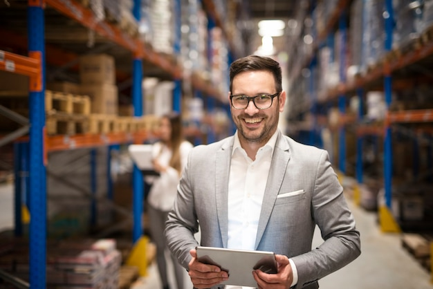 Portrait of successful middle aged manager businessman holding tablet computer in large warehouse organizing distribution