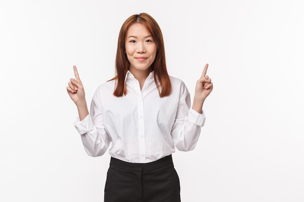 Portrait of successful pleasant asian office lady in shirt and skirt, pointing fingers down, click here gesture, smiling , invite to check-out promo, product advertisement on white wall