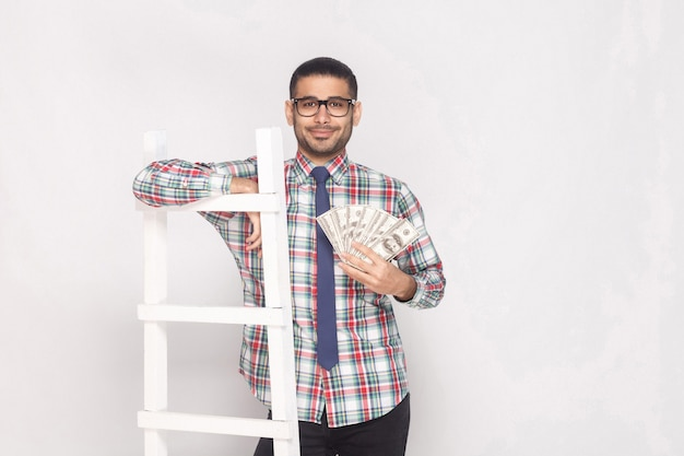 Portrait of successful rich handsome bearded young man in colorful checkered shirt with blue tie standing, holding fan of cash and lean on white stairs. indoor studio shot, isolated on grey background