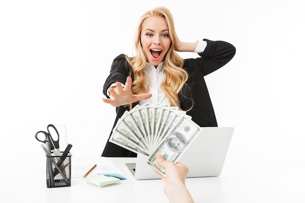 Portrait of successful woman wearing office clothing grabbing dollar bills at workplace, isolated