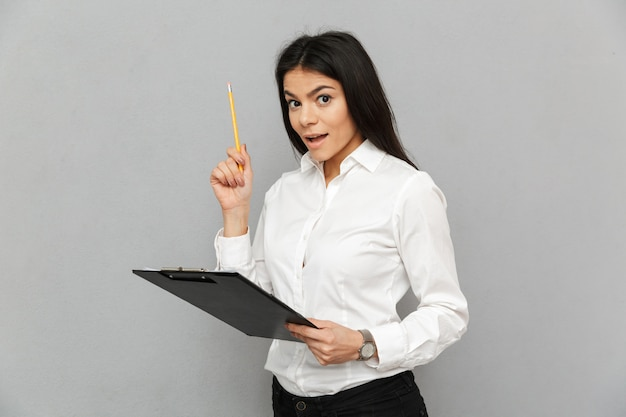 Portrait of successful woman with long dark hair wearing businesslike outfit holding clipboard with papers and examining documents, isolated over gray background