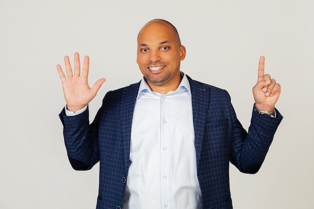 Portrait of successful young african american businessman guy, showing number six with fingers, smiling, confident and happy. the man shows six fingers. number 6.