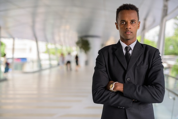 Portrait of successful young african businessman outdoors with arms crossed